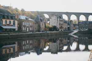 medieval arched bridge over river in old town on sunny day