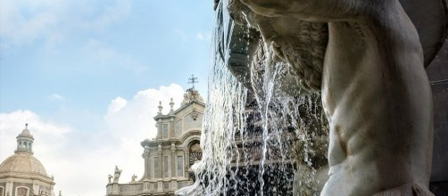 View of the cathedral in Catania through the Amenano fountain