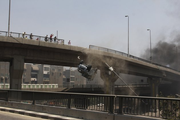 Egyptian protestors push occupied armored police vehicle off bridge