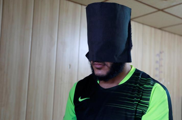 Amaar Hussein, 22, an Islamic State member, stands as his head is covered with a black hood while he waits to be escorted to his cell in Sulaimaniya, Iraq February 15, 2017. REUTERS/Zohra Bensemra