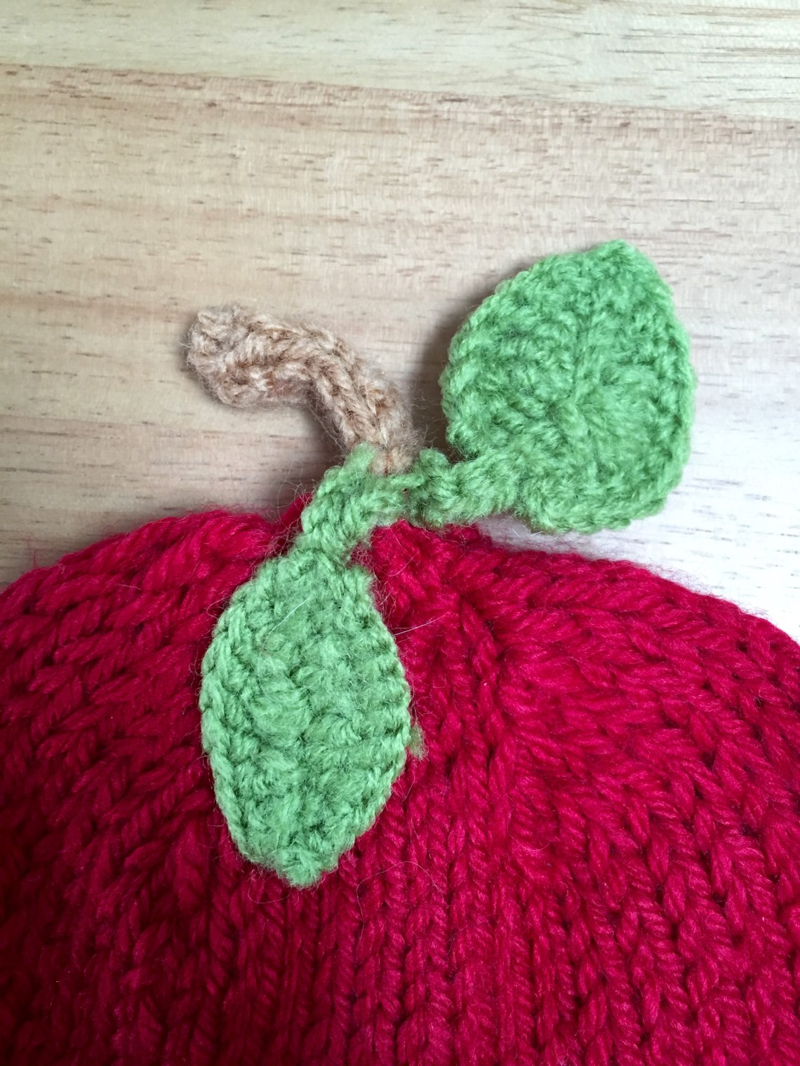 Baby hat to look like an apple with crocheted leaves