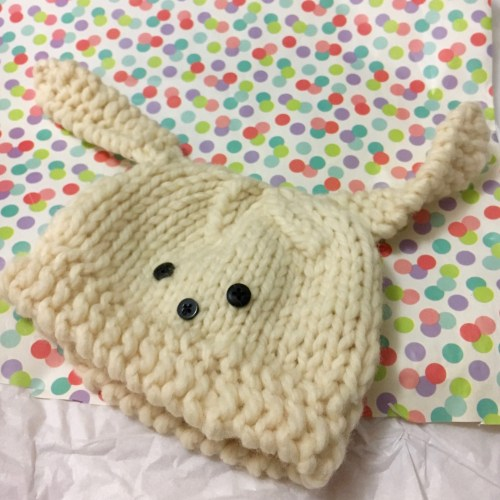 A hat which looks like a bunny on polka dot gift wrap. Baby hats are great Last minute knitted gift ideas
