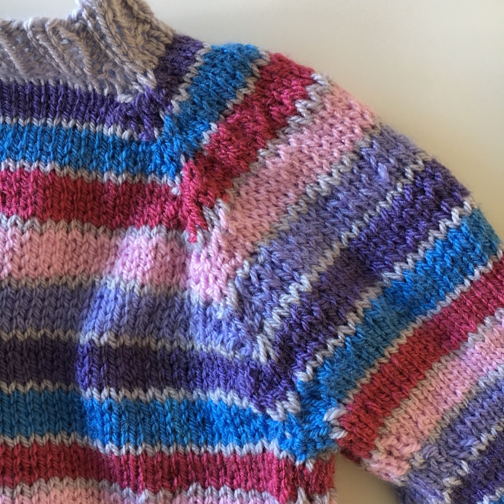 An acrylic sweater before blocking - blocking makes a huge difference to this raglan seam!