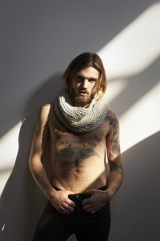 Tattooed man wearing a WOOLN scarf.