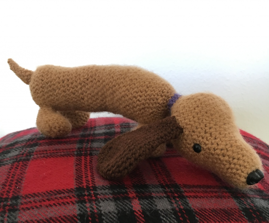Very long crocheted dachshund looking hangdog.
