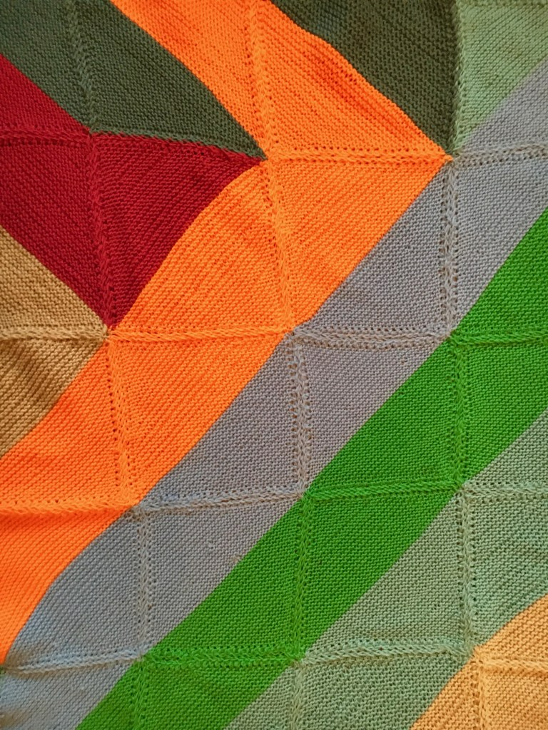 Detail of my finished welcome blanket, showing orange, blue and green stripes