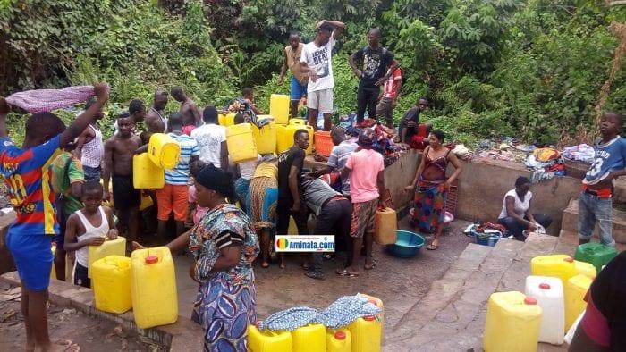 Des citoyens font la queue pour puiser de l'eau dans un quartier de Kindia