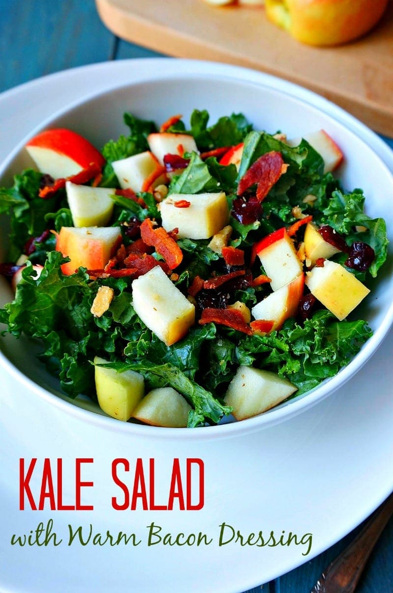 Kale Salad with Warm Bacon Dressing: Baby kale is tossed with apples, dried cranberries, toasted nuts, and bacon, then dressed with a warm and tangy dressing, taking this salad over the top