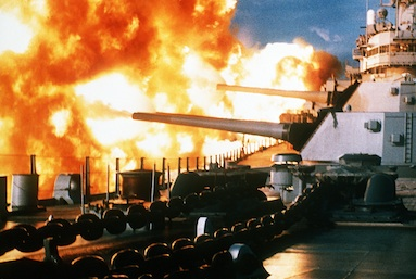 A view from the forward deck of the battleship USS NEW JERSEY (BB-62) as her 16-inch guns are fired off the starboard side during a deployment off the coast of Beirut, Lebanon.