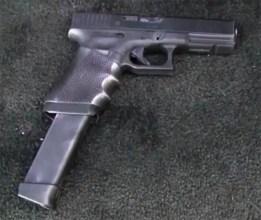 Modified Glock machine pistol with oversized ammunition magazine