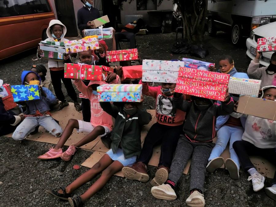 children with presents sitting