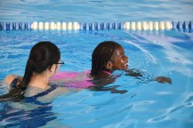 Photo by ROBIN HART/robin.hart@amnews.com Brianna Hylton is all smiles as she paddles during a swimming lesson with Katie Lamb.