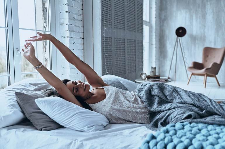 navigate the pressure to have a partner or babies, woman stretching in bed