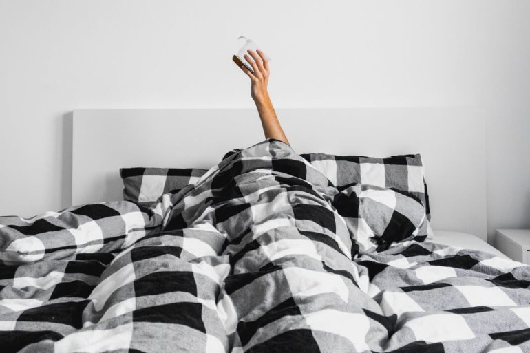 Woman in bed with sheets over her holding a cup of coffee up.