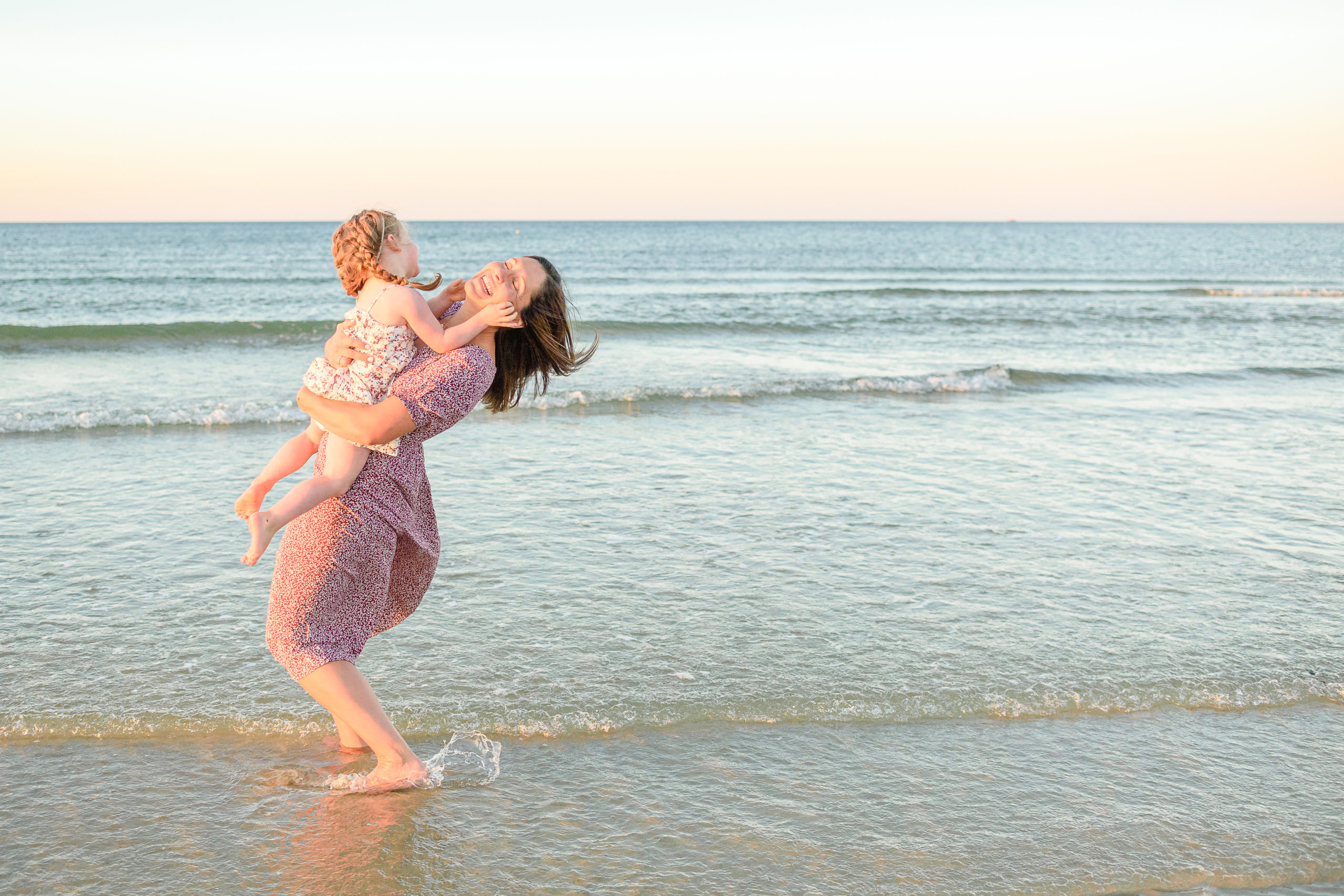 mother and daughter playing in the waves at the beach during motherhood session