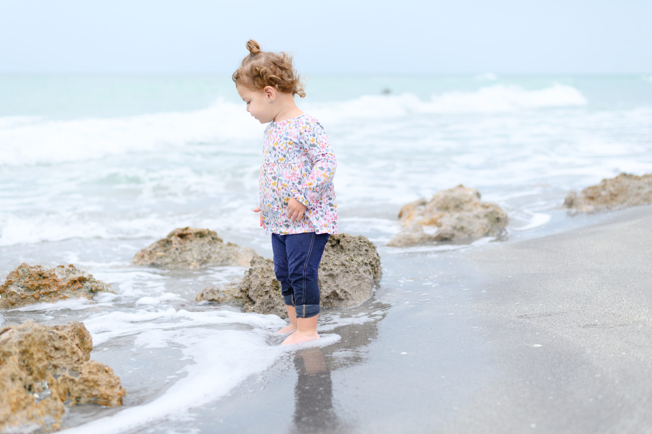 Young toddler girl with her feet in the water at the beach, admiring the way the waves crash against the large rocks. Taken during family beach session in Venice Beach