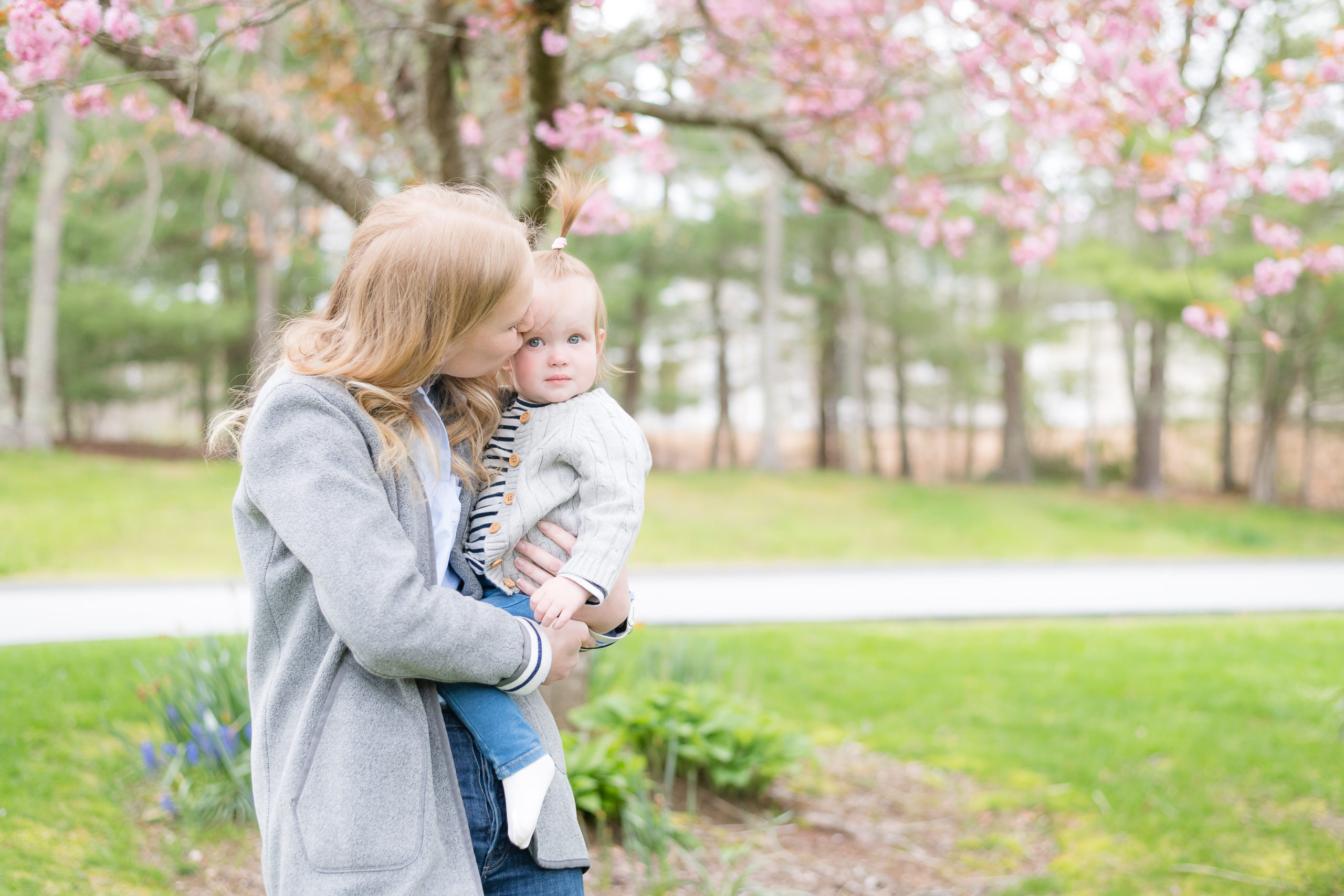 Mother kissing little girl on the cheek in front of a blooming cherry tree during Mother's Day family photoshoot