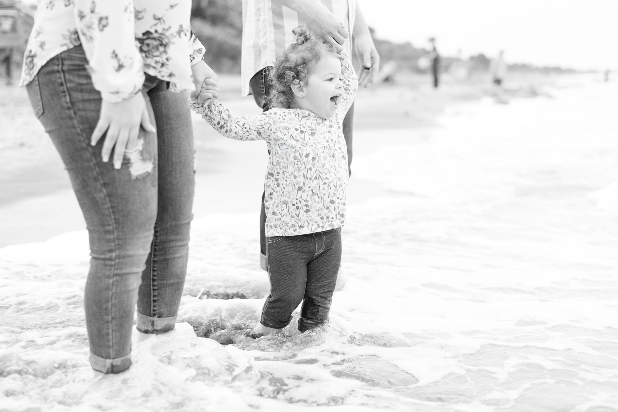 black and white image of mother and father holding little girl's hands as they gaze out to the ocean. They are standing ankle deep in the waves at the beach, enjoying this moment from their family beach session in Venice Beach, FL
