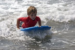 Child taking waves with a board