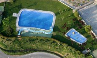Vistas-generales-de-las-piscinas-climatizadas-con-tobogan-y-forma-de-playa-en-el-Berga-Resort-bergueda-con-circuito-termal-bungalow-camping-y-actividades-para-ninos-500x300
