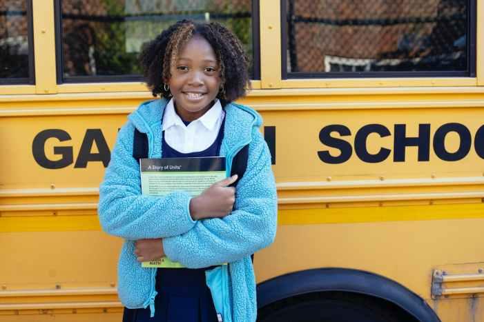 smiling black schoolgirl with textbook