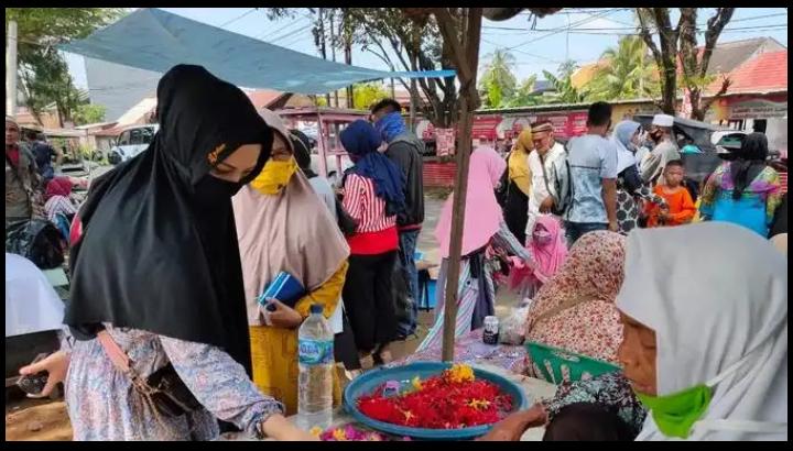 Salah satu pengunjung TPU Kandang Kawat Palembang Sumsel membeli kembang kuburan, saat akan berziarah ke makam keluarganya di lebaran hari pertama (Liputan6.com / Nefri Inge)