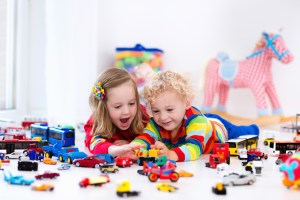 Two kids playing with legos and toys