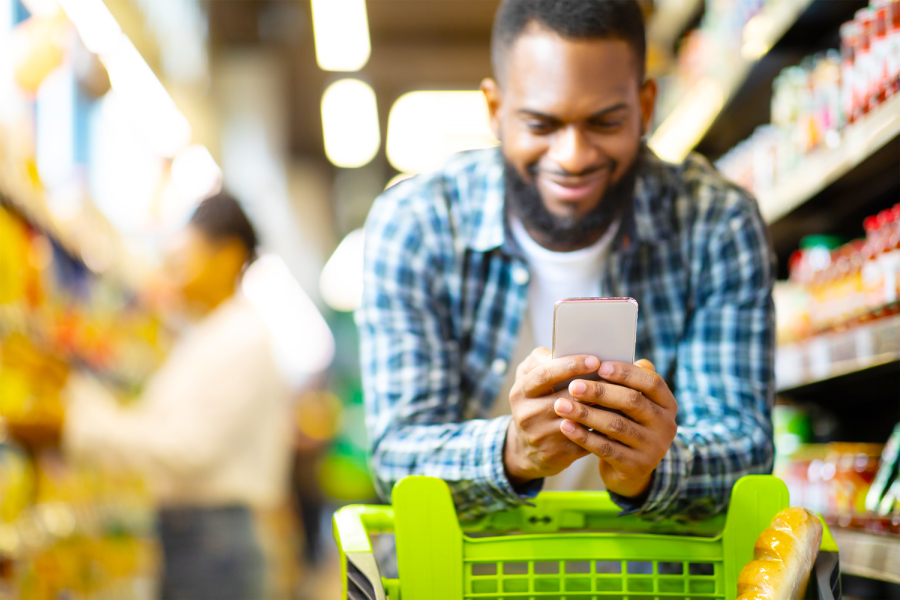 man pushing grocery cart while looking on phone