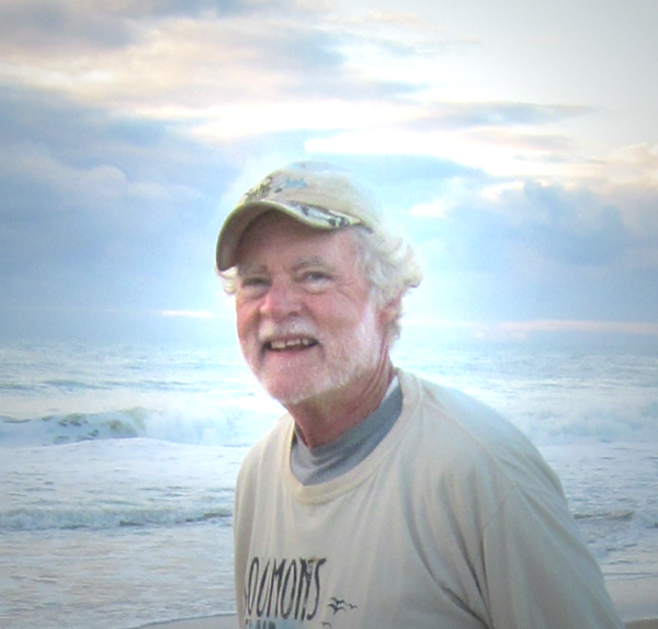 Hombre blanco con barba en gorra bronceada y camisa bronceada con un fondo oceánico brillante.