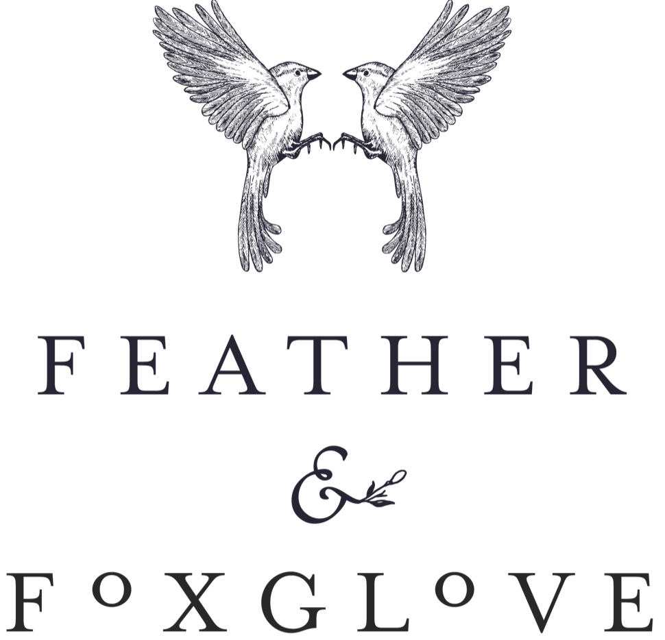 Text: Feather & Foxglove with two birds mirroring one another above the text.