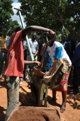 Artisans in Busia County use a brick pressing machine provided to them by the FINISH INK project to make makiga bricks