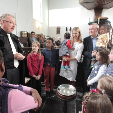 Ds Van den Berg in gesprek met de kinderen