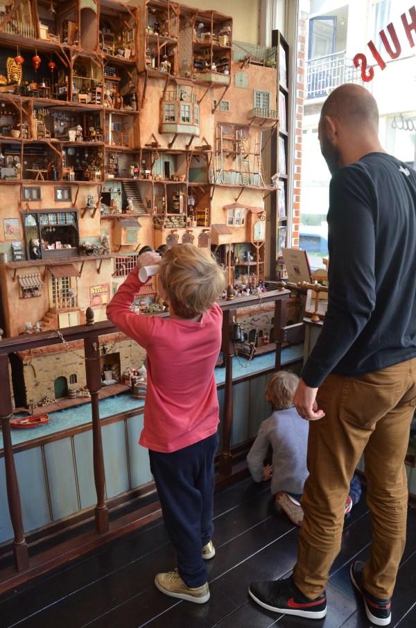 Child using binoculars to look at the mouse mansion in the Jordaan Amsterdam (Het Muizenhuis winkel & werkplaats)