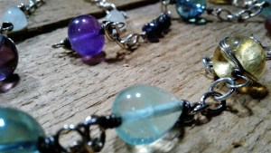 a pale green teardrop gemstone bead in the foreground with purple and blue beads on silver link chain in the background on a wooden surface