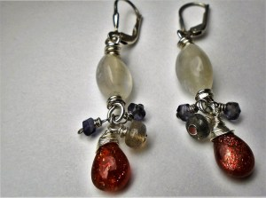 a pair of earrings with sparkly orange stones, purple-blue stones, and white stones