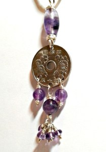 a silver coin pendant with purple gemstone beads
