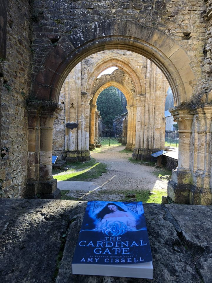 Arches from the ruins of the Orval Abbey in Belgium with the book The Cardinal Gate by Amy Cissell in the foreground.