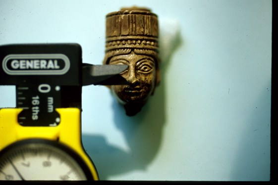 black and yellow calipers measuring tiny sculpture of a head