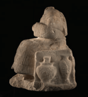 stone statue of seated woman, broken, headless