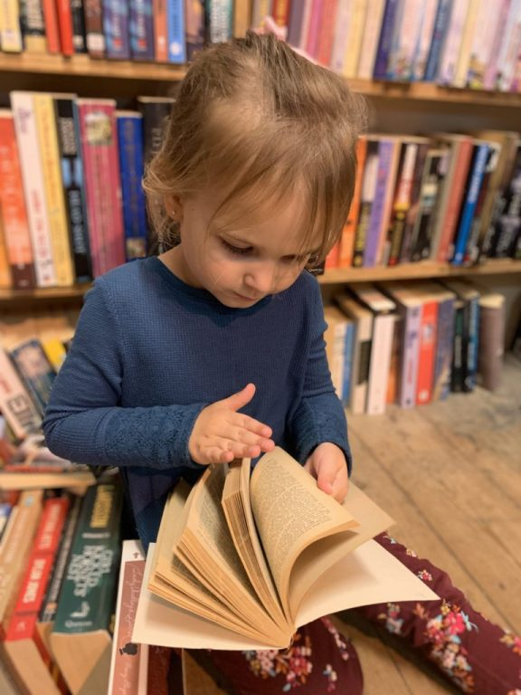 little girl flipping through pages of a book in a used book store