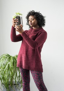 Photo of a lovely woman holding a plant wearing a deep red, tunic-length turtleneck.