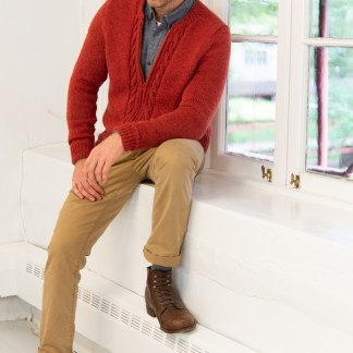A zippered, cabled hand-knit cardigan on an adult man