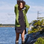 A woman at the seaside in a bright green drop shoulder cardigan.