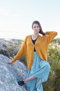 A woman next to a rock in an oversized, tapered-shaped, drop shoulder cardigan.