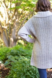View from behind of an allover lace sweater with stockinette sleeves.