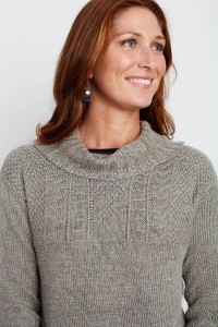 Closeup of a smiling woman in a linen drop shoulder turtleneck