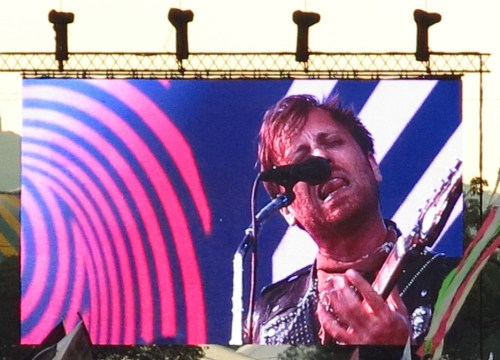 Dan Auerbach of the band The Black Keys sticking out his tongue on stage at Glastonbury.