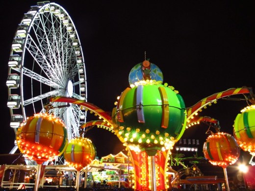 ferris wheel behind carnival ride with multiple arms at the Winter Wonderland Christmas Market in London, England's Hyde Park