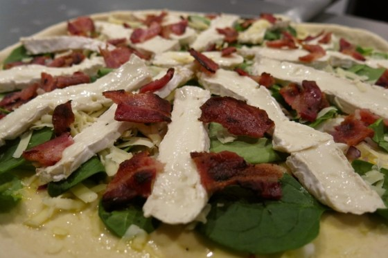 unbaked pizza topped with camembert slices, crumbled bacon, minced red onion and garlic, spinach
