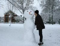 woman kisses snowman